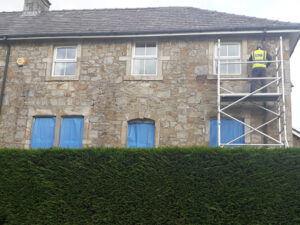 Man repointing window sill from scaffold structure