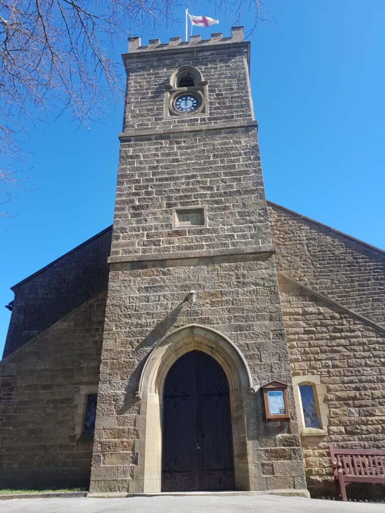 front facade of church tower in sun with clear blue sky