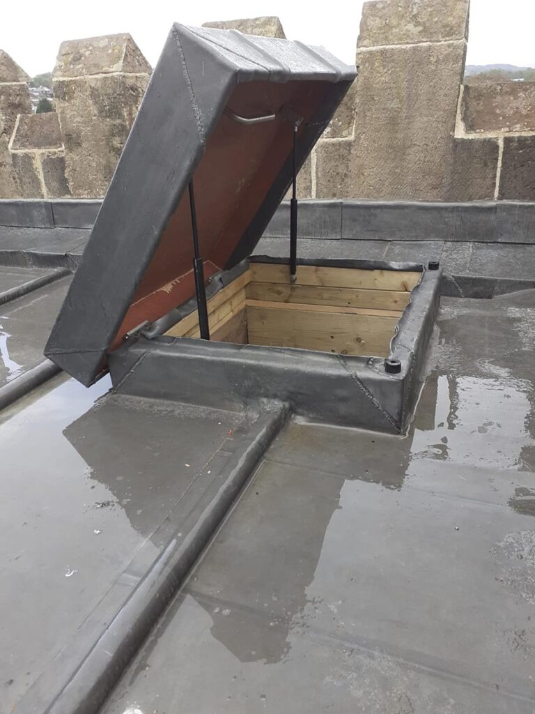 Lead covered roof access hatch opened with gas struts visible