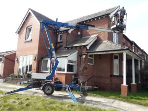 man inspecting house roof from 'cherry picker'