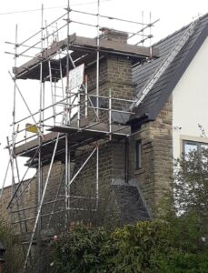 scaffold to side of house straddling chimney