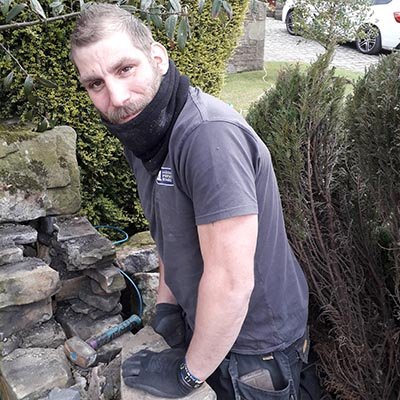 Photograph of Scott Little restoring a dry stone wall