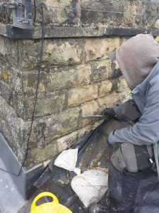 worker chiselling stone chimney