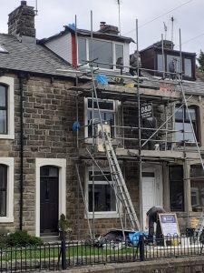 men working terraced house on scaffold