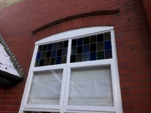 close up of tall window with leaded lights at top