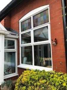 tall sash window with stained glass at top